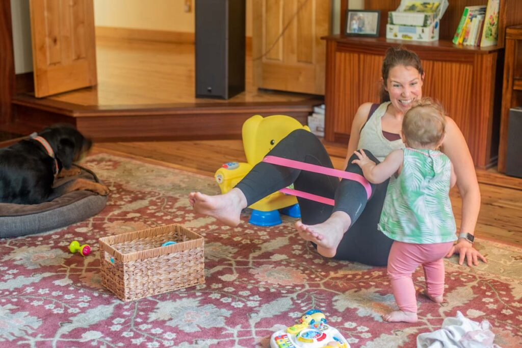 Using bands to do a floor workout with a baby.