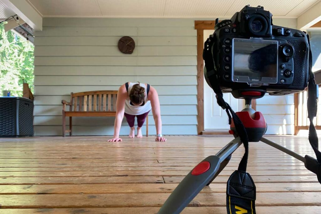 Travel-friendly Manfrotto tripod set up to take photos of woman doing planks.