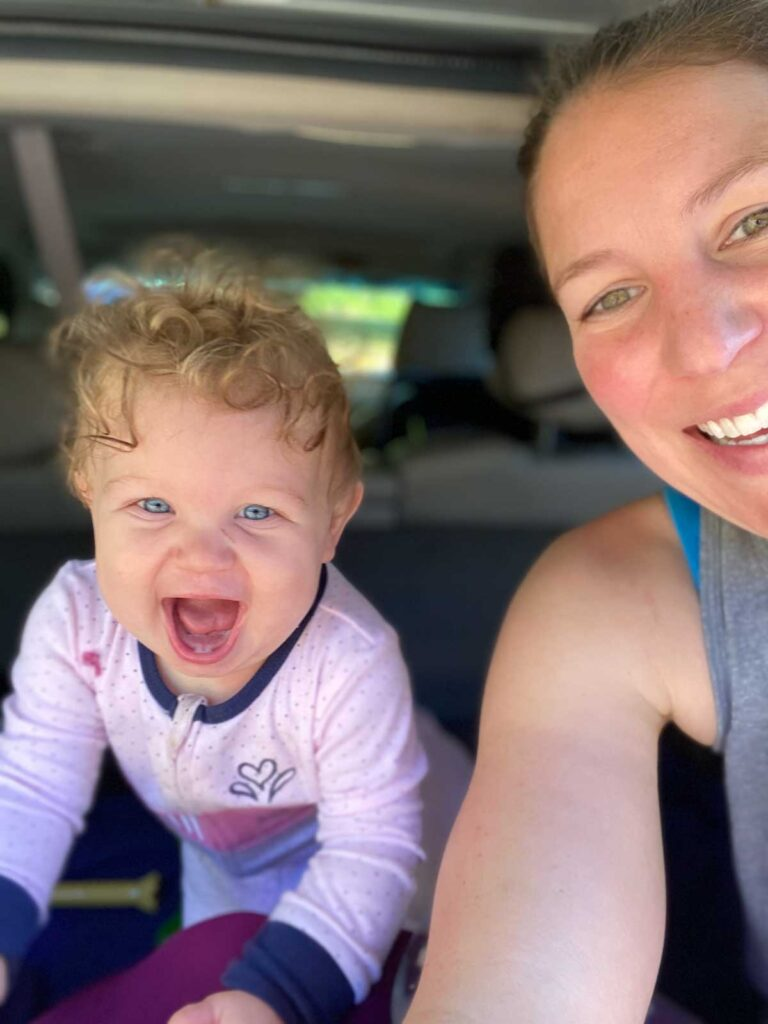 happy baby playing in back of car