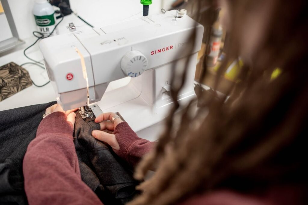 Devan Nichols sews tags onto each of her pieces.